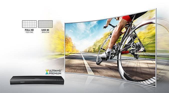 Zakrzywiony ekran telewizora SUHD, na którym wyświetlany jest doskonałej jakości obraz jadącego kolarza. W lewym dolnym rogu widoczny odtwarzacz UHD Blu-ray K8500. W lewym górnym rogu grafika porównująca rozdzielczość Full HD i UHD 4K.